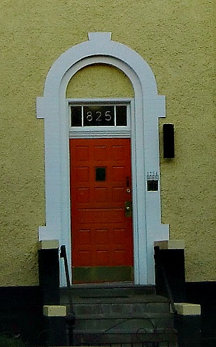 The door is unusually narrow.  The white, sthone frame helps the door seem appropriately sized for the house.