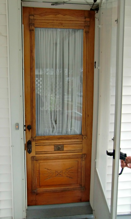 This is a beautiful wood door that is partially obscured by storm door.  A full glass storm door would be an improvement, although no storm door would look best.