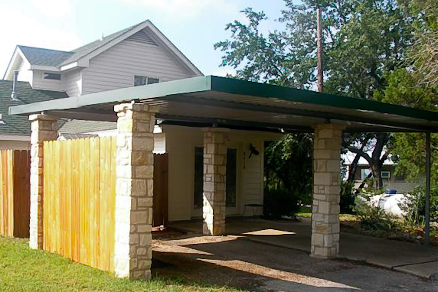Car port with flat roof and stone columns