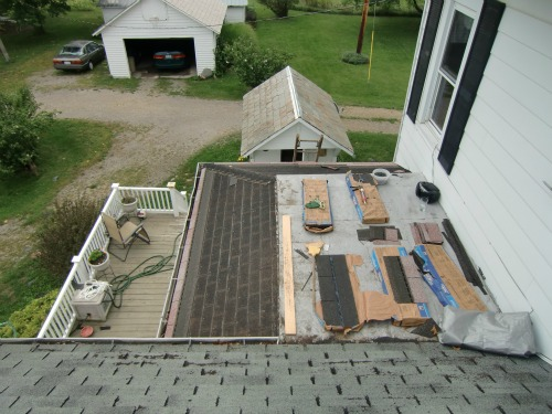 Roof Repair - Here the tabs have been cut off the small roof skirting the flat roof.
