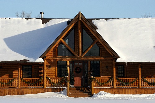 Log home plans range from rustic to modern.  This one blends contemporary windows with a traditional layout.