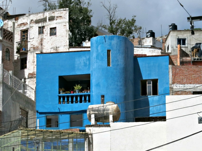 A colorful house placed on a steep slope stands out for miles. Many Mexican houses are a vibrant blue.