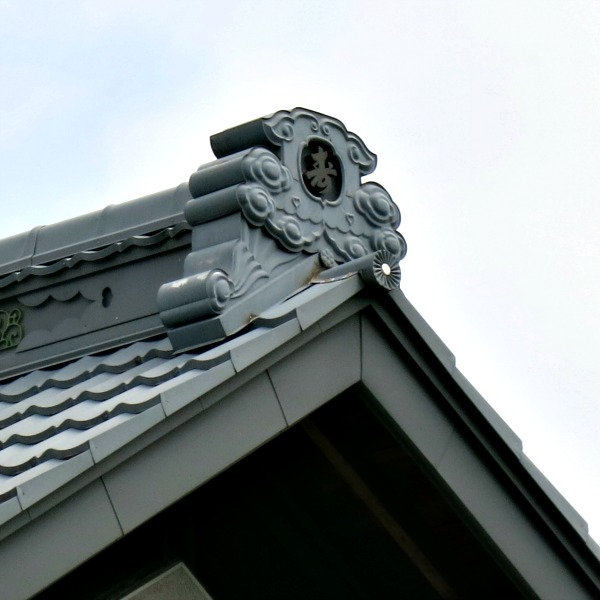A carved stone roof finial rides the ridge of a house in Japan.  These were usually decorated with the crest of the family.