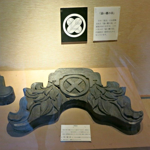 A carved roof finial on display in a museum in japan.  Not how its bottom surface is shaped to fit the tiles.