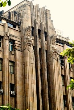 Art Deco building in Mumbai, India with two elongated statues flanking the door.  They are armed and dangerous.
