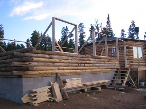 View of the log home with the walls just started