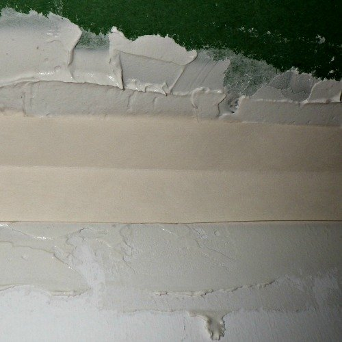 Drywall tape applied on top of mud
