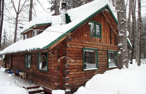 log home with green border under snow - courtesy of Iwona Kellie at Flickr