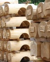 Milled logs stacked and ready for assembly of a wood home-log home plans