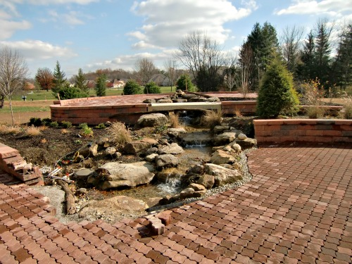 The unfinished garden with a waterfall fed by the rainwater collection system