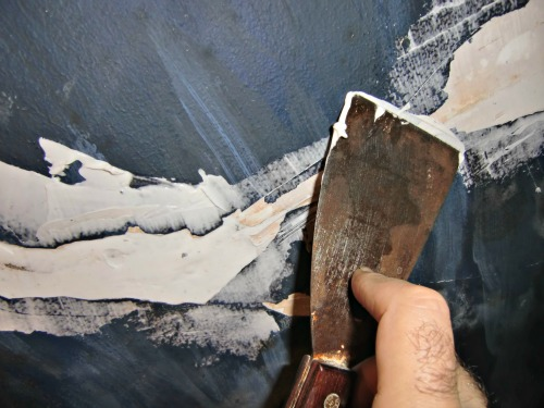 Smoothing the caulk during the plaster ceiling repair requires a wet putty knife
